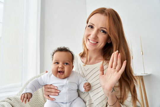 Happy young caucasian mother waving hand holding little cute funny african american baby girl daughter on lap having virtual distance meeting video call looking at camera at home, webcam view.