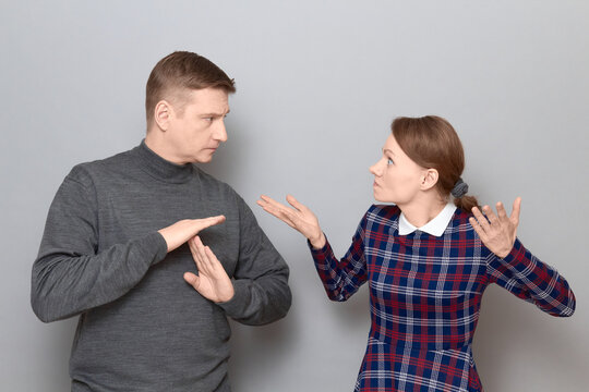 Woman is trying to explain something, man is showing stop gesture