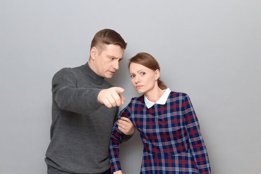 Serious man is holding woman by arm and pointing straight ahead