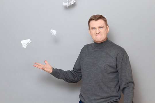Portrait of angry mature man throwing up crumpled pieces of torn paper