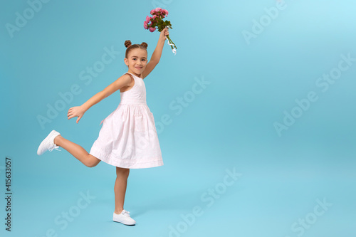happy little girl holds bouquet of roses and runs isolated on blue studio background. Mother's day.