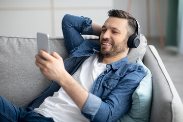 Handsome bearded man in headphones listening to music on phone