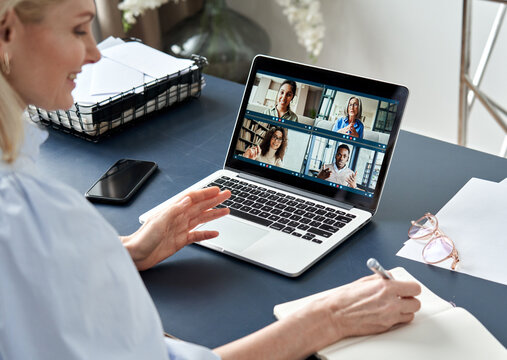 Business woman having virtual team meeting on video conference call using laptop computer. Social distance work from home office with diverse people group in remote online chat. Over shoulder view