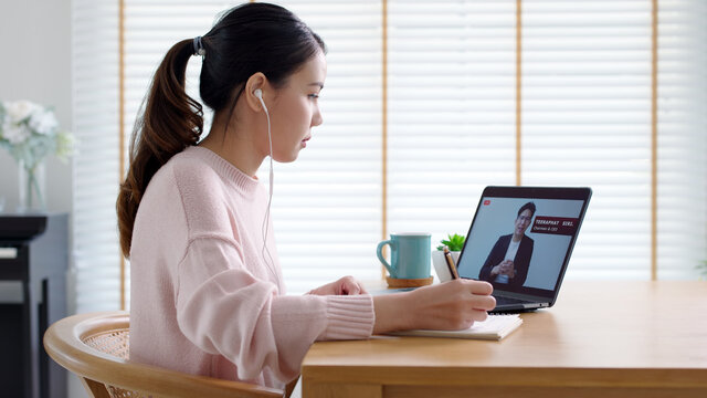 Back rear view young asian woman listen to virtual business conference webinar, management town hall or all hands meeting at home in quarantine social distance work remotely with asia speaker concept.