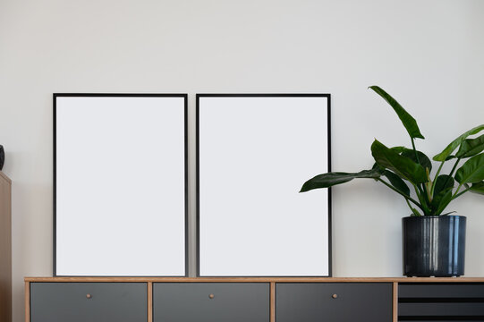 Two vertical black mockup frames on wooden design sideboard leaning agains white wall next to green plant in Scandi design