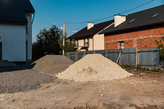 Two heaps of white sand with stones and gray rubble on a construction site. Backfill Material. Building foundation concept.