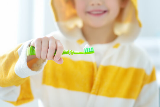 Preschooler boy cleaned teeth with dental floss and then is brushing his teeth with toothbrush carefully. Learning children proper oral hygiene. Dental medicine for kids.