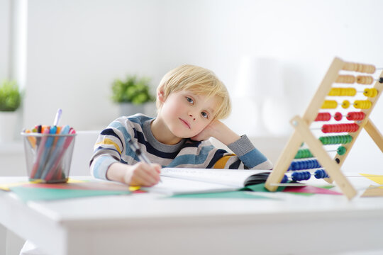 Elementary student boy doing homework at home. Child learning to count, solves arithmetic examples, doing exercises in workbook. Math tutorial. Preparing preschooler baby for school. Education