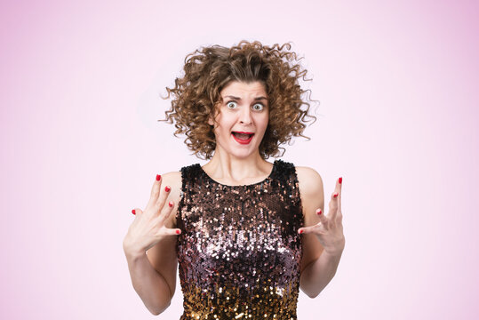 Portrait of a screaming furious young woman with open mouth on light pink background. Conflict and quarrel concept