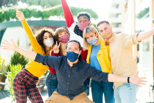 Group of multiracial people wearing protective face masks smiling at camera - New normal friendship concept with multicultural friends having fun outdoor - Focus on asian guy