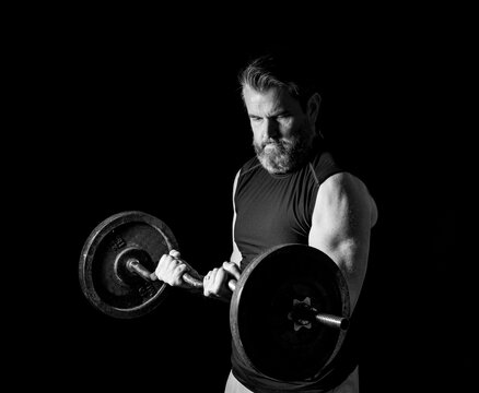 strong, active, middle aged man with gray beard lifting heavy weights in studio setting, 2 thirds profile view.