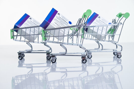 Shopping carts with Vaccine boxes with Sputnik V vaccine Gam-COVID-Vac on white table with reflection.