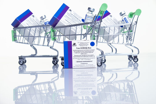 Moscow, Russia – February 10, 2021: Shopping carts with Vaccine boxes and vials with Sputnik V vaccine Gam-COVID-Vac on white table with reflection.