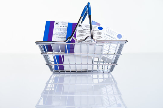 Shopping basket with Vaccine boxes with Sputnik V vaccine Gam-COVID-Vac on white table with reflection.