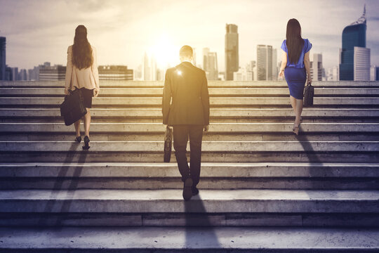 Rear view of three business people climbing stairs