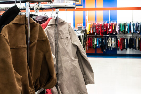 A suede jacket and a beige trench coat on a silver clothing rack in a thrift store in London, Ontario, Canada. Bokeh, soft-focus background showing kids apparel lined up on racks.
