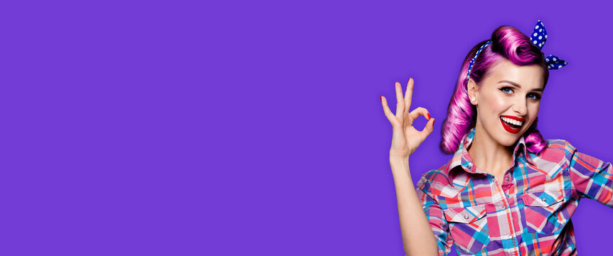 Pin up girl. Portrait photo of excited happy smiling purple hair woman showing ok hand sign gesture. Retro and vintage concept. Violet color background. Caucasian model posing at studio.
