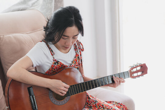 Young Asian woman play guitar. Home hobbies and recreations