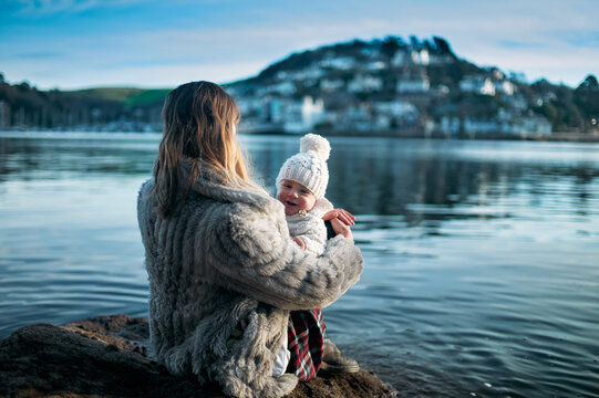 Young mother with baby in sling sitting by water in harbour