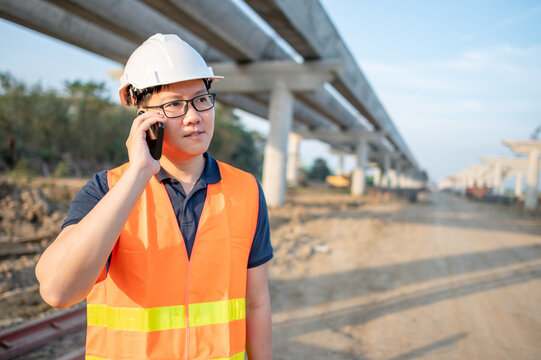 Asian worker man or male civil engineer with protective safety helmet and reflective vest using smartphone for project management at construction site.
