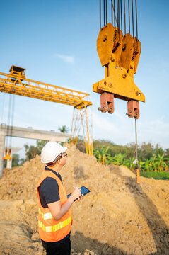 Smart Asian worker man or male civil engineer with protective safety helmet and reflective vest using digital tablet for project planning and checking crane lifting hook at construction site.