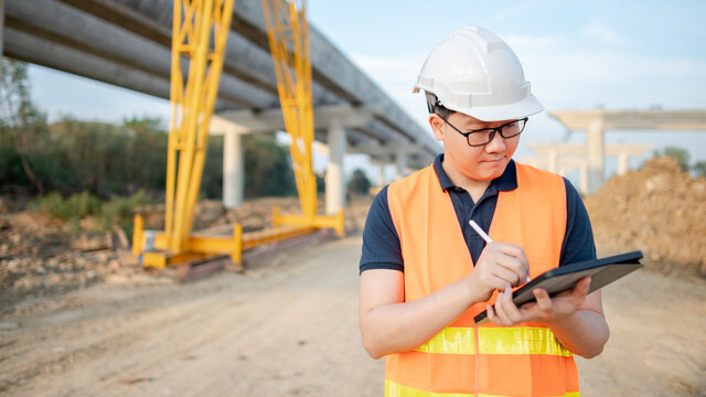 Smart Asian worker man or male civil engineer with protective safety helmet and reflective vest using digital tablet for project planning and checking architectural drawing at construction site.