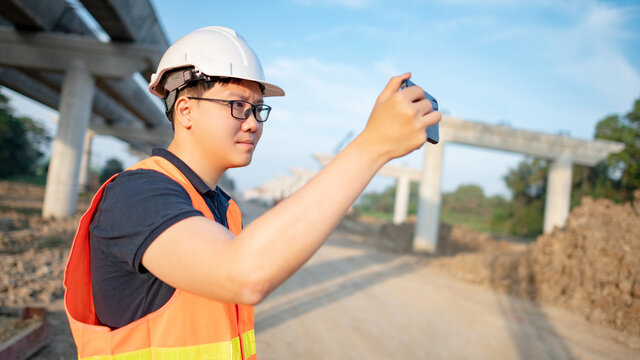 Smart Asian worker man or male civil engineer with protective safety helmet and reflective vest using using smartphone for taking photo at construction site.