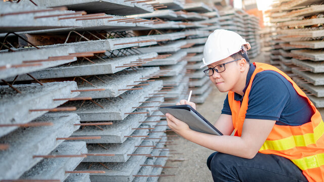 Smart Asian worker man or male civil engineer with protective safety helmet and reflective vest using digital tablet for project planning and checking material at construction site.