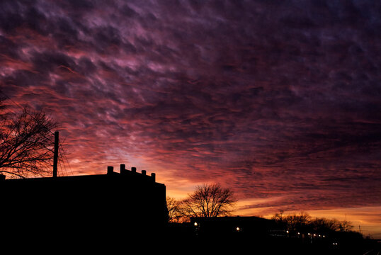 Textured Orange and Pink clouds at sunset behind silhouetted small town Missouri buildings with a row of street lamps in foreground.
