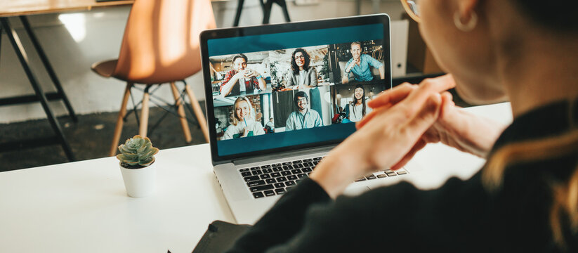 Woman has video conference with her remote team using laptop and camera