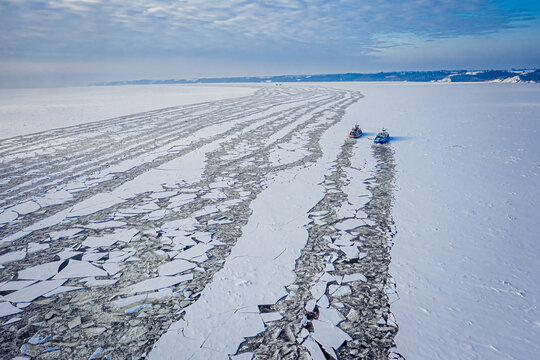 Two icebreakers crush the ice on river in winter, Poland