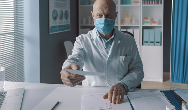 Doctor with surgical mask giving a prescription