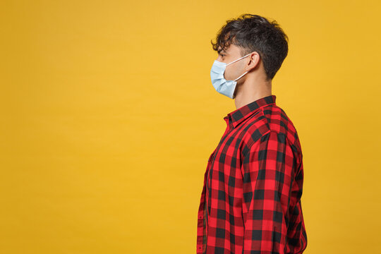 Side profile view of young spanish latinos man 20s in red checkered shirt, sterile face mask safe coronavirus virus covid19 pandemic quarantine isolated on yellow color background studio portrait.