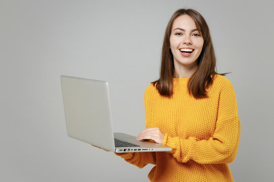 Young smiling happy freelancer copywriter positive cute attractive caucasian woman 20s wear casual knitted yellow sweater hold laptop pc computer isolated on grey color background studio portrait