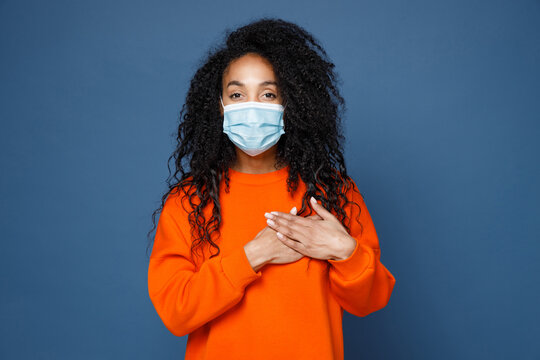 Pretty young african american woman in casual orange sweatshirt sterile face mask to safe from coronavirus virus covid-19 holding hands on heart isolated on blue color background studio portrait.