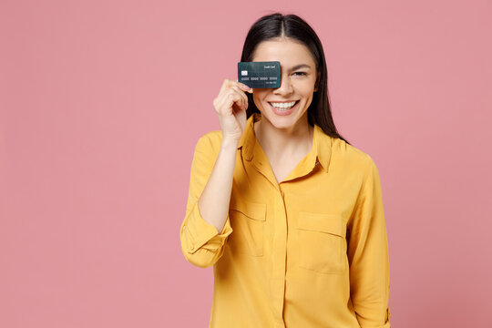 Young latin happy overjoyed smiling fun happy cheerful galdden attractive woman in yellow shirt covering eye with credit bank card looking camera isolated on pastel pink background studio portrait