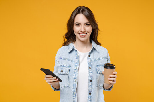 Young smiling successful happy brunette positive woman 20s in stylish denim shirt white t-shirt holding plastic cup of hot coffee mobile cell phone isolated on yellow color background studio portrait.