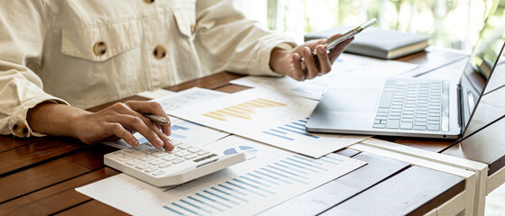Obraz The businesswoman is using a white calculator to check company financial information, she is checking company financial information from the documents provided by the finance department. - fototapety do salonu