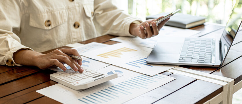 The businesswoman is using a white calculator to check company financial information, she is checking company financial information from the documents provided by the finance department.