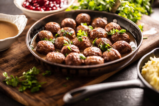 Swedish meatballs, kottbullar, in a pan topped with fresh parsley