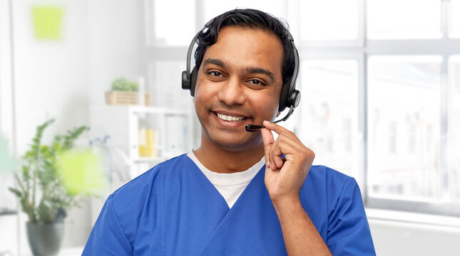 medicine, profession and healthcare concept - happy smiling indian doctor or male nurse with headset over medical office at hospital background