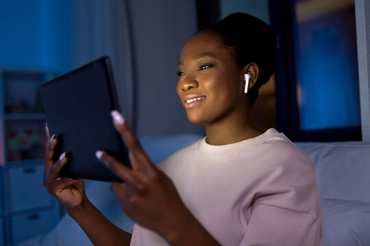 technology, internet and people concept - happy smiling young african american woman with tablet pc computer and wireless earphones lying in bed at home at night