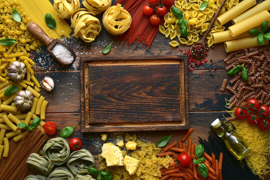 Traditional ingredients of italian cuisine : pasta, parmesan cheese, olive oil, basil, garlic and spices on a dark wooden background. Top view with copy space.