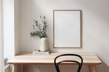 Obraz Home office concept. Old books, empty vertical wooden picture frame mockup hanging on white wall. Wooden desk, table. Vase with olive branches. Elegant working space. Scandinavian interior design. - fototapety do salonu