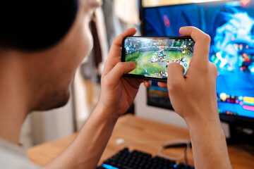 Fototapeta Unshaven brunette guy playing video game on his mobile phone obraz