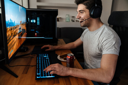 Happy brunette guy in headphones playing video game on his computer