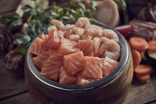 Appetizing raw salmon and shrimps in bowl in kitchen
