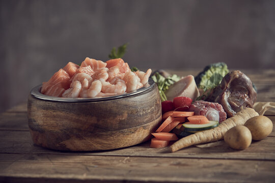 Bowl with raw fresh seafood near various cut ingredients