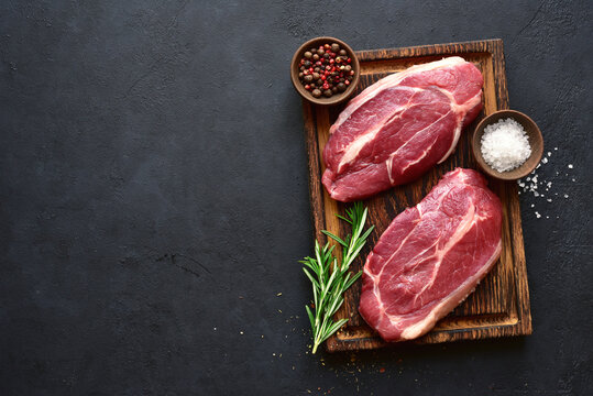Raw organic marbled beef steaks with spices  on a wooden cutting board . Top view with copy space.