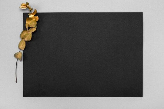 Black invitation card mockup with a dried eucalyptus decoration on a neutral table. 5x7 ratio, similar to A4, A5. minimalistic design